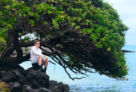 Handsome Caucasian man in forties sitting on rocky shore of hawaiian beach, by Chinaman's Hat island