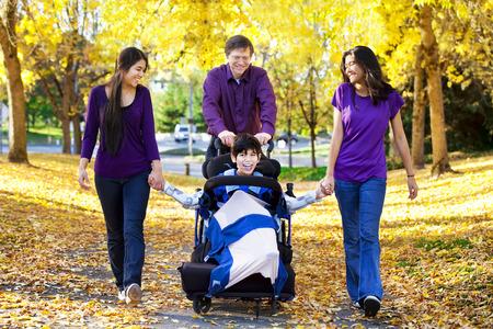 秋の歩行車椅子で障害児の多民族の家族の葉します。