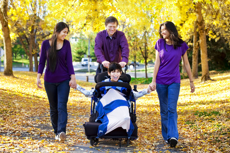 Multiracial family with disabled child in wheelchair walking among autumn leaves