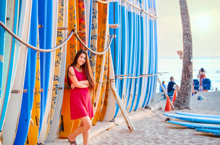 Beautiful biracial teen girl in red dress leaning against rack of surfboards on beach in Hawaii Stockfoto