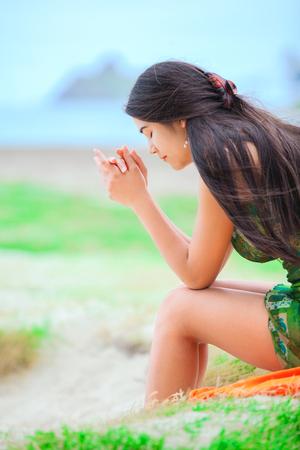 Beautiful biracial teen girl in green sundress sitting at tropical Hawaiian beach, praying.