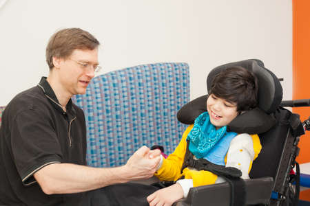 Father playing with disabled biracial son sitting in wheelchair while waiting in doctor's office, laughing together.