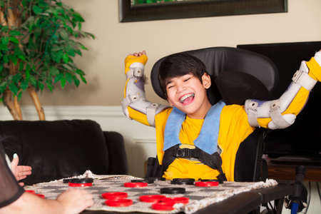 Young biracial disabled boy in wheelchair playing checkers at home. Child has cerebral palsy. Stock Photo