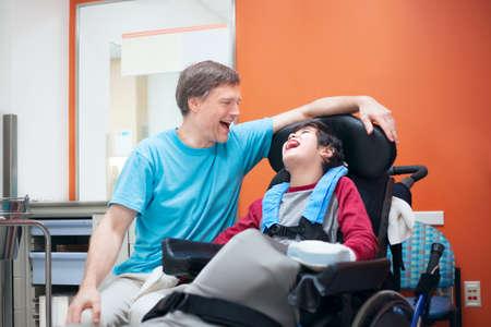 Padre hablando con el hijo birracial discapacitados sentado en la silla de ruedas mientras espera en la oficina del doctor, riendo juntos.
