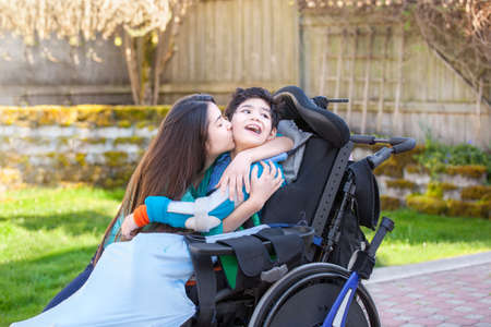 Sister kissing and hugging disabled little nine year old  brother in wheelchair outdoors Stock Photo
