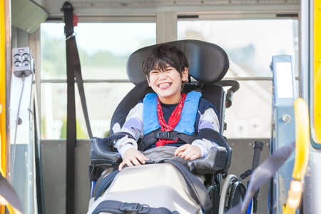 Happy biracial little boy with special needs sitting in wheelchair, riding on yellow school bus lift, going to school Stockfoto