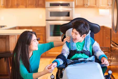 Negen jaar oude gehandicapte jongen in een rolstoel lachen met tiener zus in de keuken Stockfoto