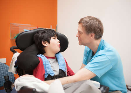 Father talking with disabled biracial son sitting in wheelchair while waiting in doctors office, laughing together.