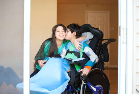 Sister kissing and hugging disabled little nine year old  brother in wheelchair indoors