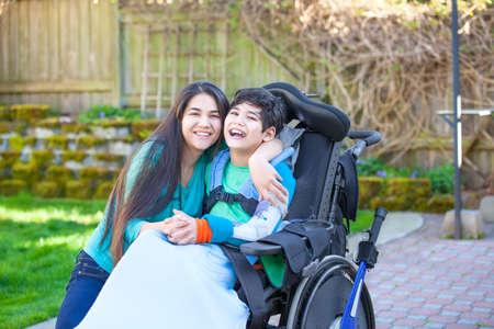 Lächelnde Jugendliche mit Behinderungen neun Jahre alten Bruder im Rollstuhl umarmt im Freien Standard-Bild - 62589994