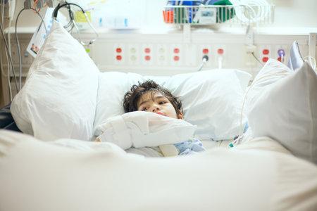 Apuesto pequeño discapacitado niño de nueve años que miente enfermo en cama de hospital. El niño tiene parálisis cerebral Foto de archivo - 63040018