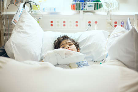 Handsome little disabled nine year old boy lying sick in hospital bed.  Child has cerebral palsy Stock Photo