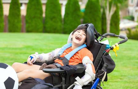 Diez años de edad niño discapacitado en silla de ruedas birracial jugando con balón de fútbol en el parque Foto de archivo