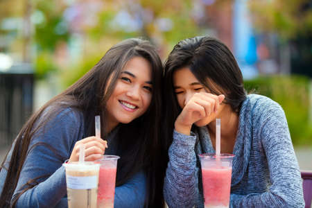 Two biracial teen girls or young women sitting together drinking boba tea at cafe, laughing and smiling Stock Photo