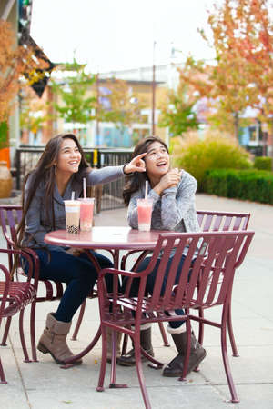 Two biracial teen girls or young women sitting together drinking boba tea at cafe, pointing and looking over at side Stock Photo