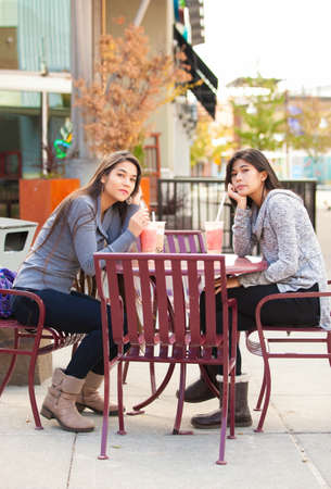 Two biracial teen girls or young women sitting together drinking boba tea at outdoor cafe, looking directly at camera