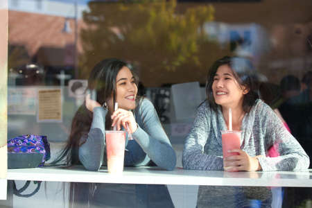 Two biracial teen girls or young women sitting together drinking boba tea inside cafe at counter