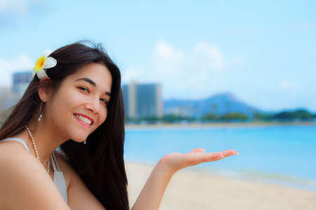 Smiling teen girl, or young woman, plumeria in long black hair, sitting on beach in Honolulu, Oahu with Diamond Head in the background. Hand palms up for product placement 免版税图像