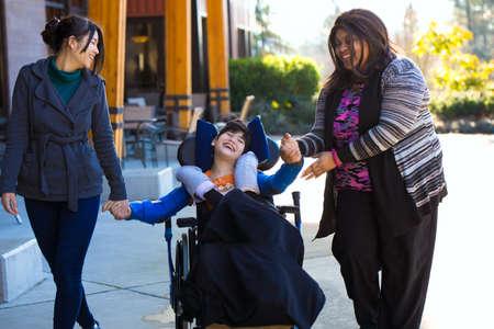 Ragazzo disabile biraziale di undici anni in sedia a rotelle che si tiene per mano con i badanti mentre su una passeggiata all'aperto