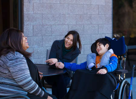 Eleven year old disabled biracial Asian Caucasian boy in wheelchair outdoors, sitting and talking with his two multiethnic caregivers Stock fotó - 96436749