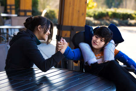 Handsome biracial Asian Caucasian disabled boy in wheelchair playing arm wrestling with sister or caregiver outdoors