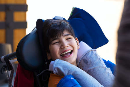 Biracial Asian Caucasian disabled boy in wheelchair smiling outdoors. He has cerebral palsy.