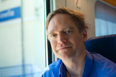 Caucasian man in forties wearing blue shirt sitting on commuter train Reklamní fotografie