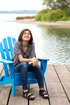 Biracial Asian Caucasian teen girl sitting on blue adirondack chair outdoors by lake, smiling 免版税图像