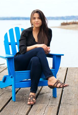 Ragazza teenager caucasica tailandese biraziale seduta in sedia blu adirondack sul molo di legno dal lago all'aperto