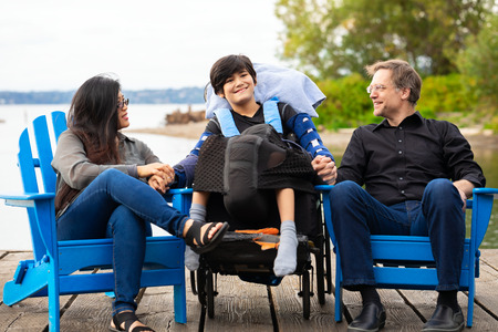 Multiracial couple sitting with disabled twelve year old son in wheelchair while sitting in blue adirondack chairs on wooden pier by lake on summer day Imagens