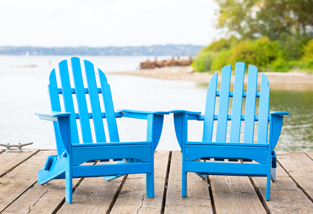Two empty blue adirondack chairs on wooden pier by lake in summer