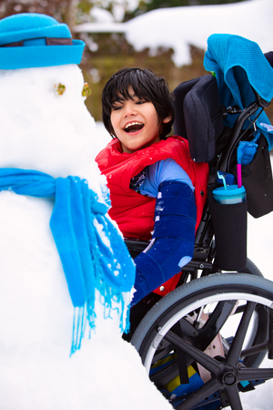 Happy smiling disabled boy in wheelchair building a snowman