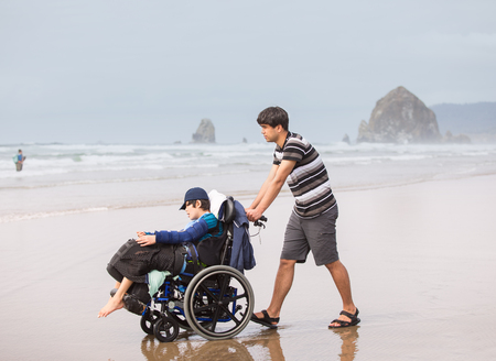 Young man pushing disabled twelve year old brother in wheelchair on a misty foggy beach by the ocean