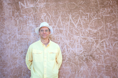 Caucasian man in late forties standing in front of concrete wall inscribed with peoples names and markings in Italy Banco de Imagens