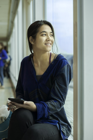 Teen girl or young woman sitting along large sunny windows at airport waiting for flight, looking out window and holding cell phone Stock Photo