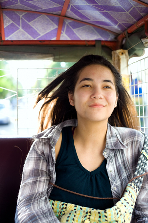 Biracial teen girl or young woman tourist riding in tuktuk taxi in Phnom Pehn, Cambodia Stock Photo