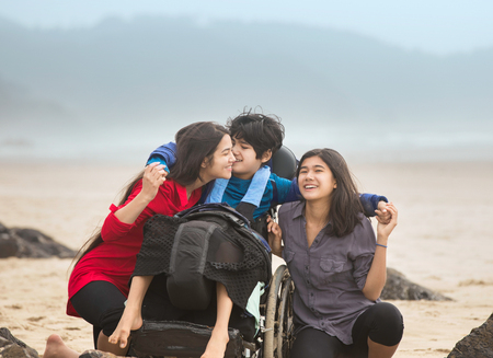 Disabled younger brother in wheelchair laughing and giving older sistesr a hug while they sit together by ocean on misty foggy beach