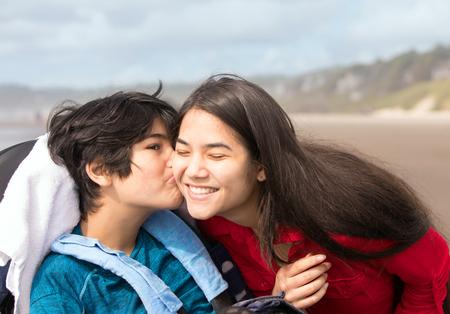 Biracial twelve year old disabled little boy in wheelchair kissing older sister on cheek Stock fotó