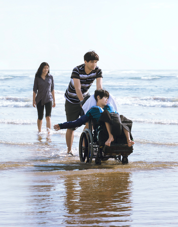 Older brother and sister walking younger disabled brotherin wheelchair in the water along the beach at ocean in summer time Stock fotó