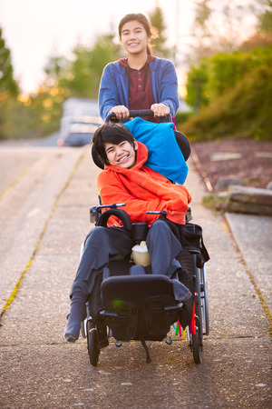 Big sister pushing disabled little brother in wheelchair around neighborhood, laughing and smiling 写真素材