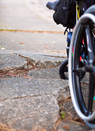 Wheelchair wheel stuck against large cracks in broken sidewalk pavement Stockfoto