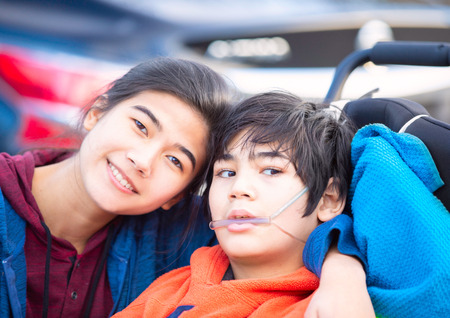 Biracial big sister lovingly hugging disabled little brother in wheelchairoutdoors, smiling