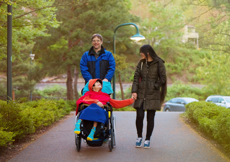 Disabled twelve year old biracial boy in wheelchair walking with father and older sister at park in cold weather