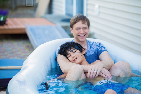 Caucasian father sitting in hottub with biracial disabled son outdoors together laughing