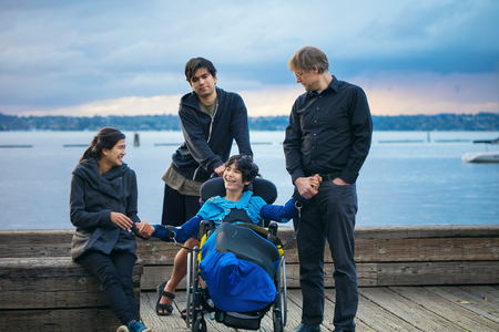 Mixed race family with disabled little boy in wheelchair outdoors on wooden pier by lake on cloudy evening at sunset in early autumn