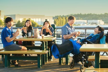 Mixed race family with disabled little boy in wheelchair eating burgers outdoors by lake