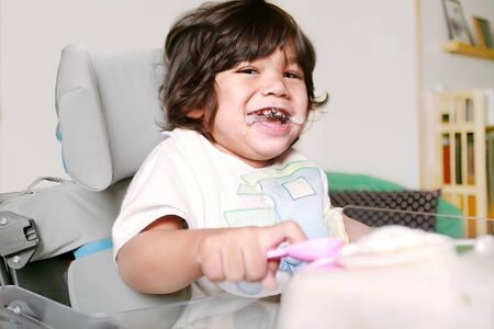 Handsome biracial disabled boy toddler sitting in wheelchairwith mouthguard smiling and playing with toys and wearing a bib