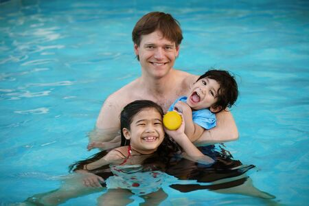 Caucasian father in swimming pool with two children, holding his disabled son in his arms