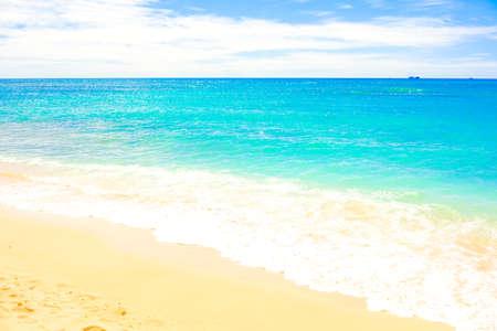 Beautiful clear blue aqua ocean waves with seafoam on warm sandy beach