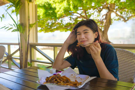 Smiling biracial Asian teen girl sitting at outdoor restaurant along beach in Waikiki, Honolulu, Hawaii eating french fries on sunny afternoon